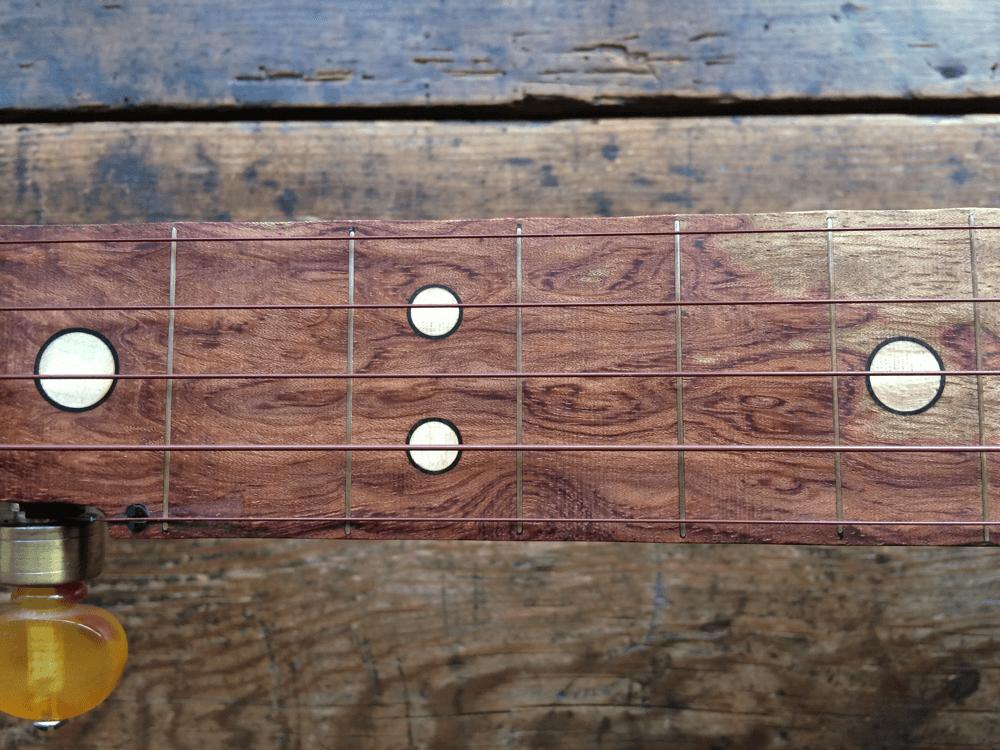 Scalloped Bubinga fingerboard close-up showing the grain pattern