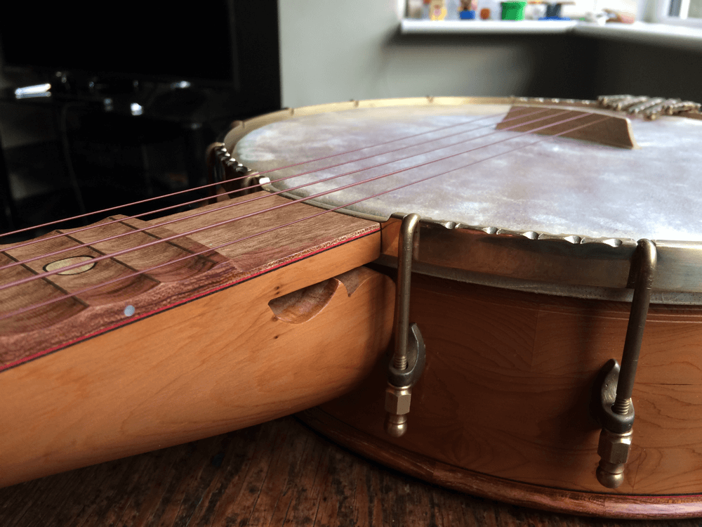 Yew banjo with scalloped fingerboard heel area