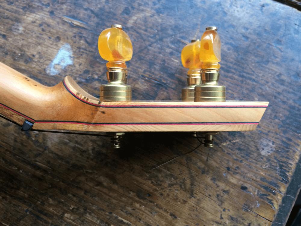 Yew banjo peg head side view showing pinstripes